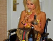 blonde wheelchair woman drinking glass of wine with bottle